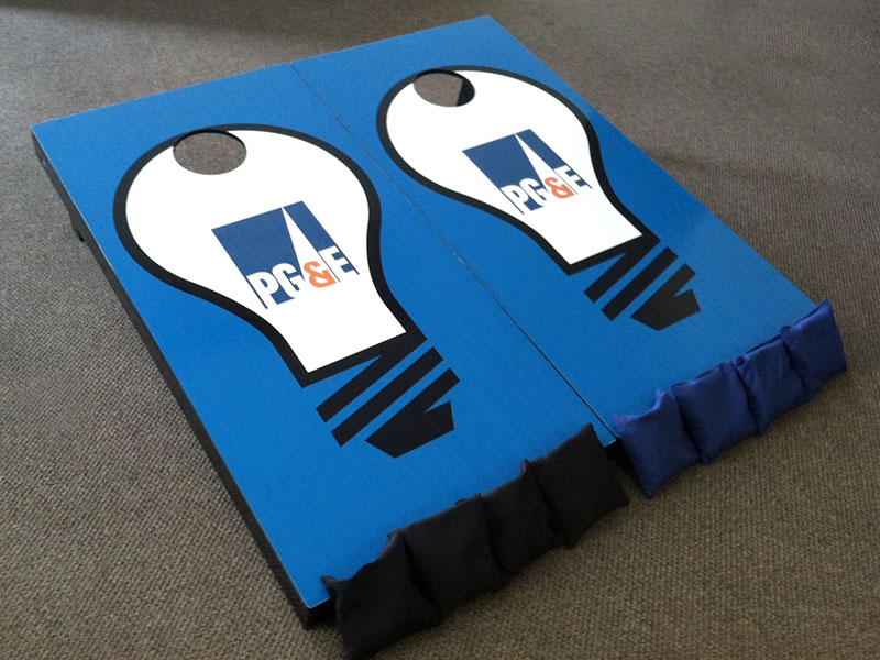 Custom cornhole game boards & bags with PG & E light bulb logo – by IWI Wood Products